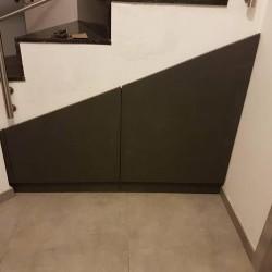 Placard noir avec tiroirs placé sous un escalier